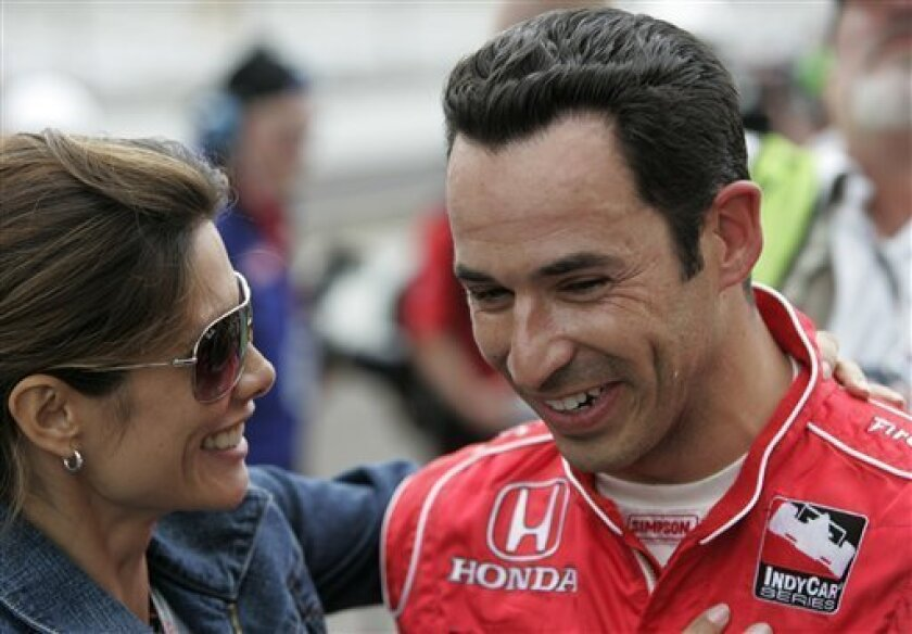 Helio Castroneves, of Brazil, is congratulated by his girlfriend, Adriana Henao, after qualifying on the provisional pole on the first day of qualifications for the Indianapolis 500 auto race at Indianapolis Motor Speedway in Indianapolis, Saturday, May 9, 2009. (AP Photo/AJ Mast)