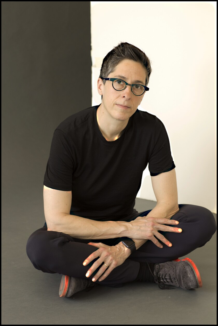 Alison Bechdel wears all black while sitting cross-legged for a portrait.