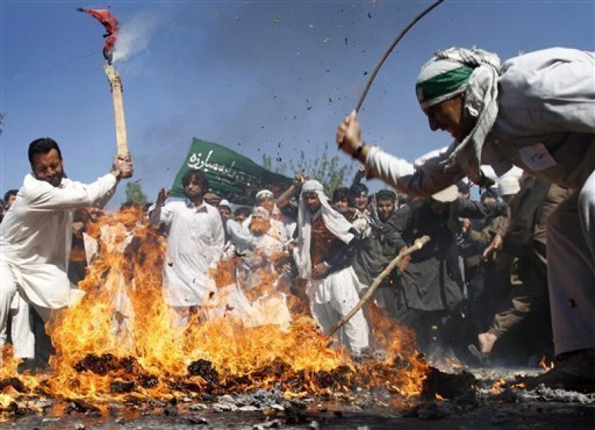 Afghan protestors beat a burning effigy of U.S. President Barack Obama during a demonstration in Jalalabad, Afghanistan on Sunday, April 3, 2011. Afghan protests against the burning of a Quran in Florida entered a third day with a demonstration in the major eastern city Sunday, while the Taliban called on people to rise up, blaming government forces for any violence. (AP Photo/Rahmat Gul)