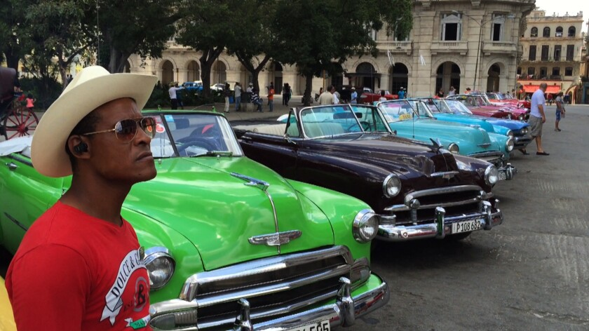 HAVANA, CUBA -- TUESDAY, MAY 5, 2015: Vintage American cars across the street from El Capitola in H