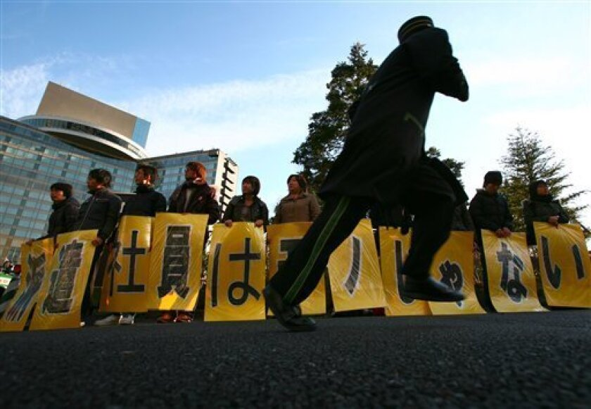 """In this Jan. 6, 2009 photo, a group of laid-off temporary workers stage a protest outside a hotel where the Japan Business Federation chairman and business circles are holding a new year's party in Tokyo. Japan's jobless rate stood at 4.8 percent, up from 4.4 percent in February, the Ministry of Internal Affairs and Communications said Friday, May 1, 2009. The actual number of unemployed jumped 25 percent from a year earlier to 3.35 million, while the number of employed workers fell 1.4 percent. The placards held by the laid-off workers read: """"Temporary workers are not properties."""" (AP Photo/Junji Kurokawa)"""