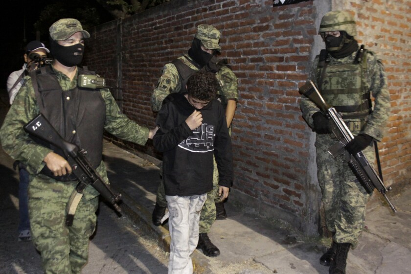 """Mexican soldiers present Edgar Jimenez Lugo, known as """"El Ponchis,"""" to the media in the city of Cuernavaca in 2010."""