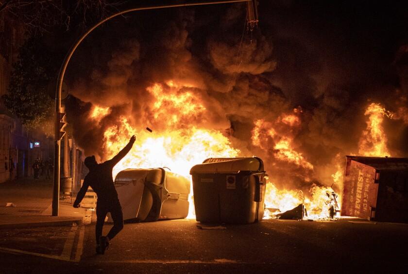 Gente reunida junto a una barricada en llamas durante las protestas por el encarcelamiento del rapero Pablo Hasél