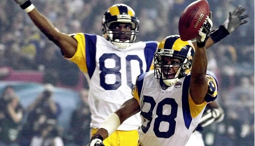 St. Louis Rams wide receiver Torry Holt and teammate Isaac Bruce celebrate Holt's touchdown catch during second half of Super Bowl XXXIV at the Georgia Dome in Atlanta on Jan. 30, 2000.