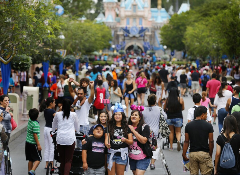 Visitors to Disneyland during its 60th Anniversary Diamond Jubilee use a selfie stick to take a photo on June 10, 2015.