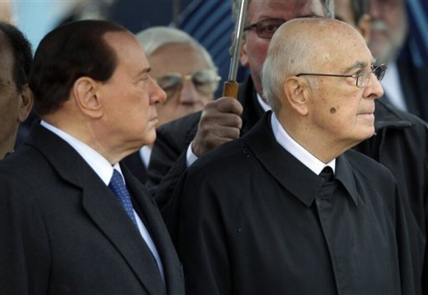 Italian President Giorgio Napolitano, right, and Premier Silvio Berlusconi attend the ceremony for the arrival of the four soldiers who died in Afghanistan on Saturday when a bomb exploded as a convoy passed insurgents and troops came under fire, at the Ciampino military airport, near Rome, Monday, Oct. 11, 2010. (AP Photo/Andrew Medichini)