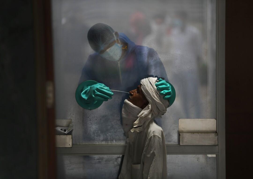 A health worker takes a nasal swab