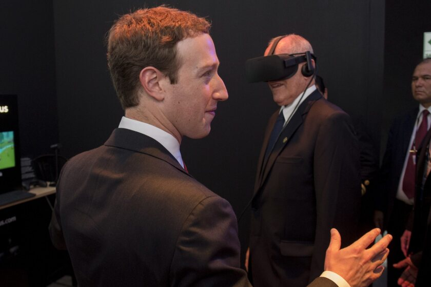 Facebook CEO Mark Zuckerberg speaks to journalists as Peruvian President Pedro Pablo Kuczynski tries out a virtual-reality headset during the Asia Pacific Economic Cooperation Forum (APEC) in Lima, Peru on Nov. 19.