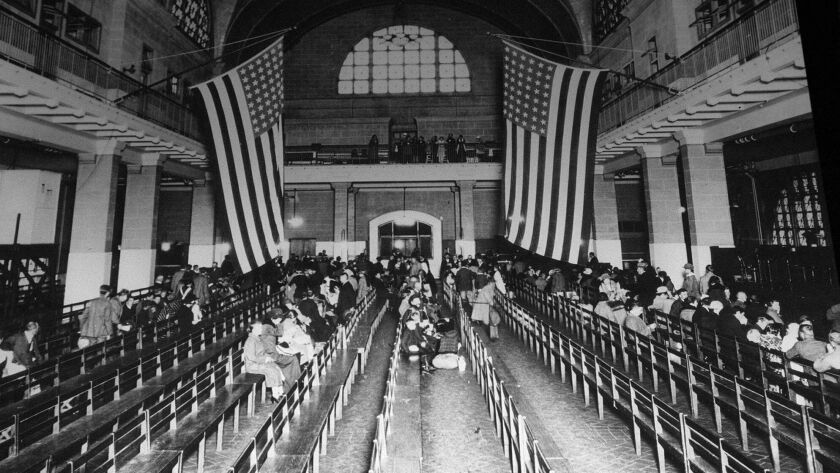 FILE - In this 1924 file photo, immigrants from Europe sit in the registry room at Ellis Island in N
