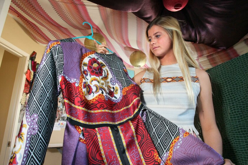 """Peytie Slater, 15, holds one of her recent creations in her home studio in Carlsbad. She recently showed her clothes at New York Fashion Week as a finalist on Lifetime network's """"Project Runway: Junior."""""""