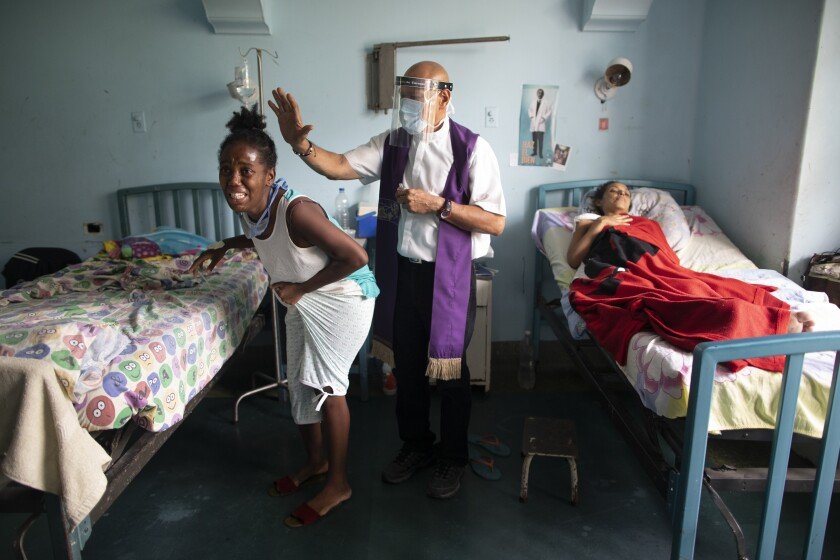 Father Felix Mendoza, a Venezuelan Catholic priest, center, prays over a woman who cries, saying she is in physical pain, at a public hospital in Caracas, Venezuela, Tuesday, May 11, 2021, amid the new coronavirus pandemic. Father Felix has been visiting patients at the hospital to comfort the sick, for the last 20 years. (AP Photo/Ariana Cubillos)