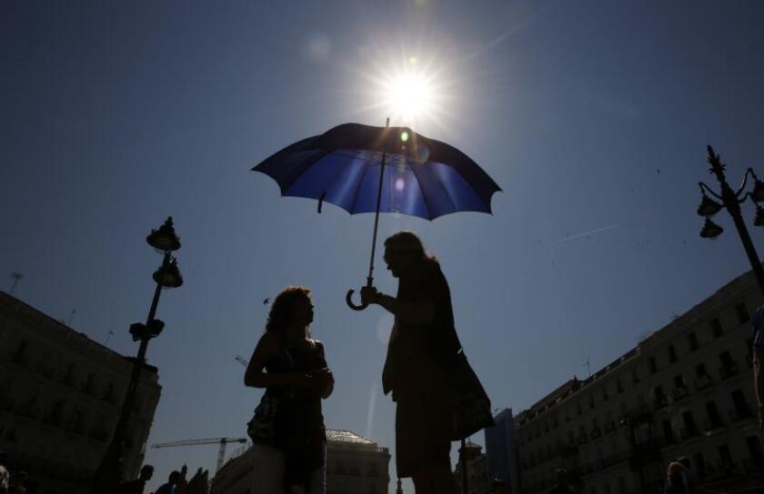 Una pareja se protege del intenso sol bajo un paraguas. EFE/Archivo