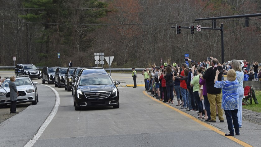 People watch as the hearse carrying the body of Billy Graham leaves Asheville, N.C., Saturday, Feb.