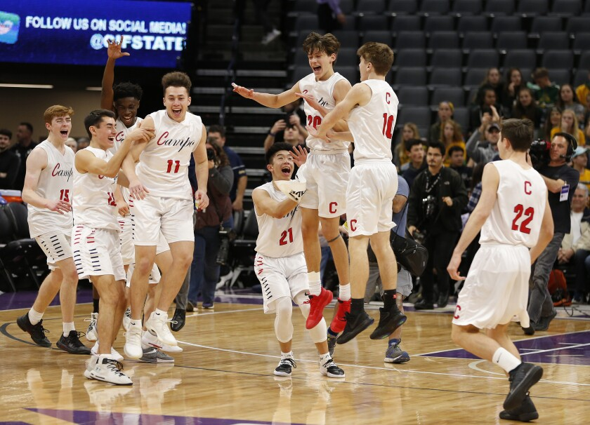 FILE - In this March 9, 2019, file photo, Campolindo players celebrate a win over Colony in the CIF boys' Division II state high school basketball championship game in Sacramento, Calif. On Thursday, March 4, 2021, lawyers representing two high school athletes say Gov. Gavin Newsom's administration has agreed to allow all indoor youth sports to resume as part of a lawsuit settlement. (AP Photo/Rich Pedroncelli, File)