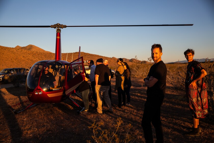 People invited to the Betaspace party wait their turn to catch a ride on the helicopter.