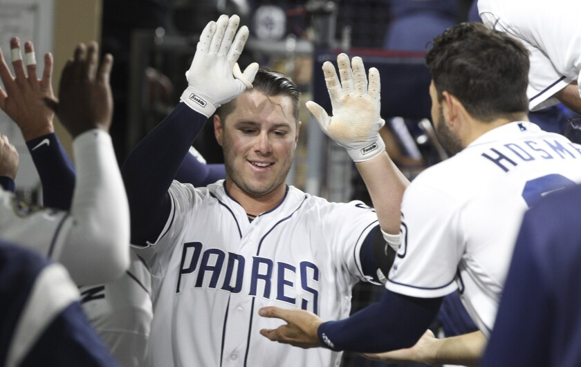 Ty France celebrates a home run in the Padres dugout.