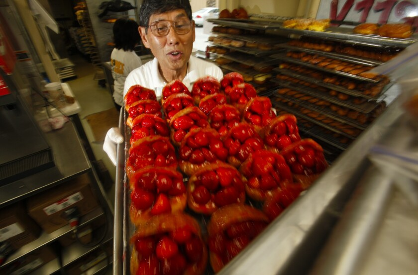 The Donut Man founder Jim Nakano with a tray of his strawberry donuts in 2011. The shop will expand to downtown L.A.'s Grand Central Market next year.