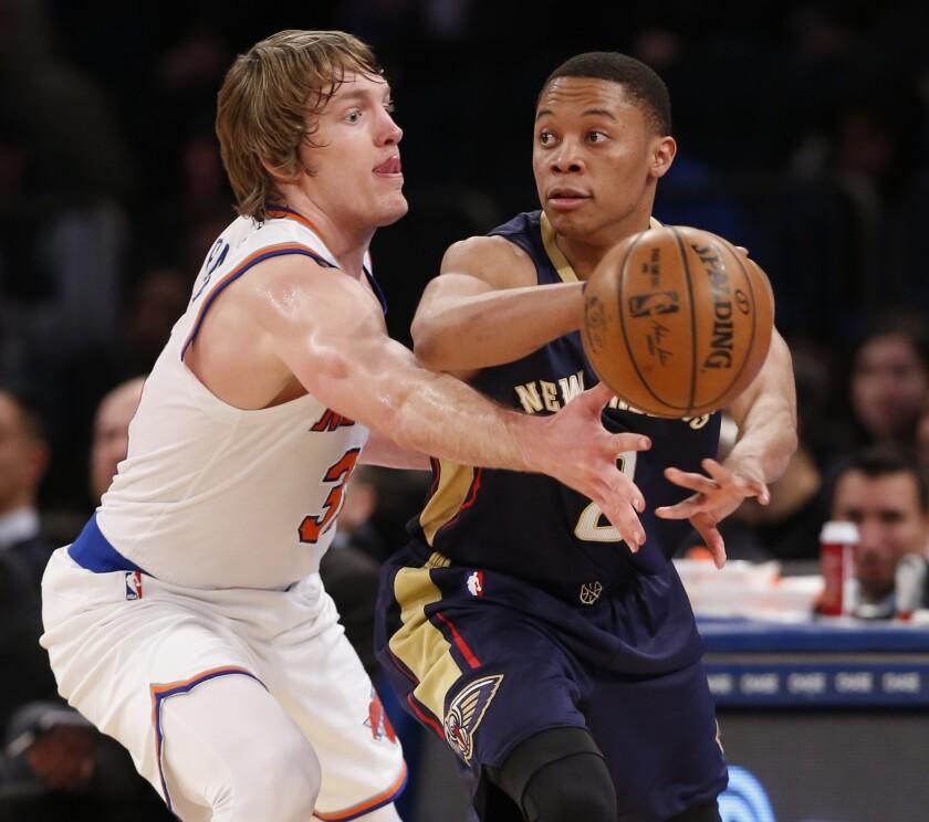 El escolta de los Pelicans de Nueva Orleans, Tim Frazier, pasa ante la defensa del jugador de los Knicks de Nueva York, Ron Baker.