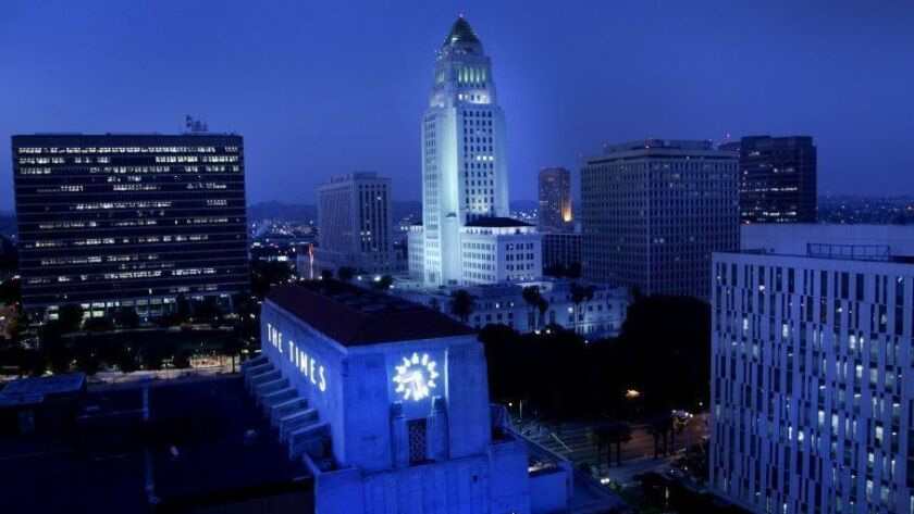 Los Angeles City Hall, with the old L.A. Times building in the foreground, is seen at night.