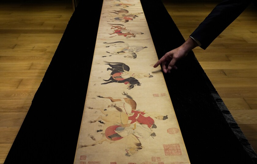 """A Sotheby's employee presents the Chinese scroll """"Five Drunken Princes Returning on Horseback"""" during a media preview"""