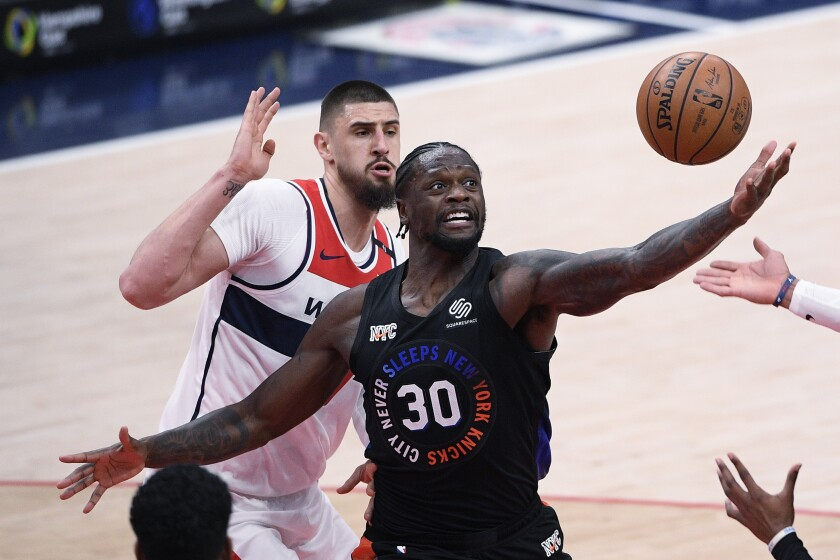 New York Knicks forward Julius Randle (30) reaches for the ball in front of Washington Wizards center Alex Len, back, during the second half of an NBA basketball game Friday, Feb. 12, 2021, in Washington. (AP Photo/Nick Wass)