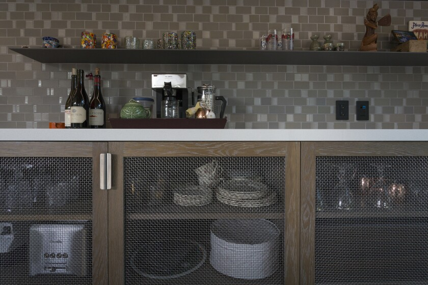 Pig wire serves as screens for kitchen shelves at the house of Jenn McCabe, her partner Lee Frees, and their dog Hank.