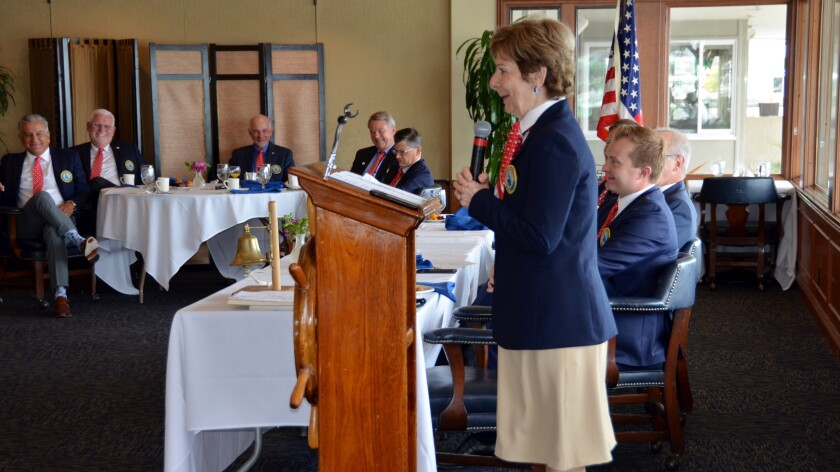 Marie Case, first female skipper of the Commodores Club, Newport Beach, conducts the final meeting of her term Friday.
