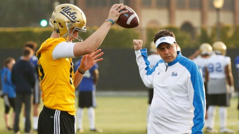 Jedd Fisch, right, works with quarterback Matt Lynch during practice on April 6.