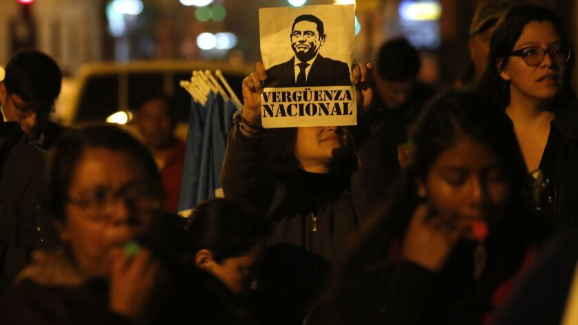 """A woman holds up a sign with portrait of Guatemalan President Jimmy Morales that reads in Spanish """"n"""