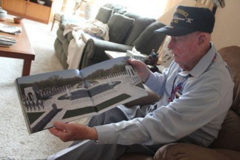 Carl 'Dusty' Dustin displays a photo of the National World War II Memorial, which he visited in October as part of an Honor Flight trip to Washington, D.C. with other World War II veterans.