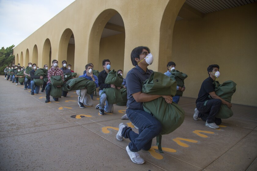 New recruits with Echo Company, 2nd Recruit Training Battalion, respond to orders during receiving at Marine Corps Recruit Depot in San Diego on Monday. Echo Company arrived at the depot three weeks ago and have been quarantined at a San Diego hotel since.