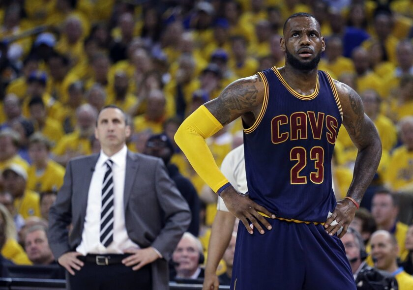 FILE - In this June 7, 2015, file photo, Cleveland Cavaliers forward LeBron James stands on the court near coach David Blatt during Game 2 of basketball's NBA Finals against the Golden State Warriors in Oakland, Calif. James' calculating image wasn't helped when the Cavaliers stunningly fired Blatt on Friday, Jan. 22, despite Blatt leading the team to the NBA Finals last season and an Eastern Conference-best 30-11 record this season. James has played for three coaches during his two stints in Cleveland. (AP Photo/Ben Margot, File)