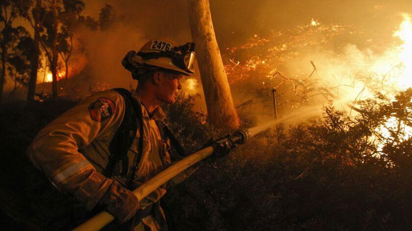 SAN DIEGO, December 7, 2017 | Cal Fire firefighter Cole Bellatti hoses a hillside on fire behind sto