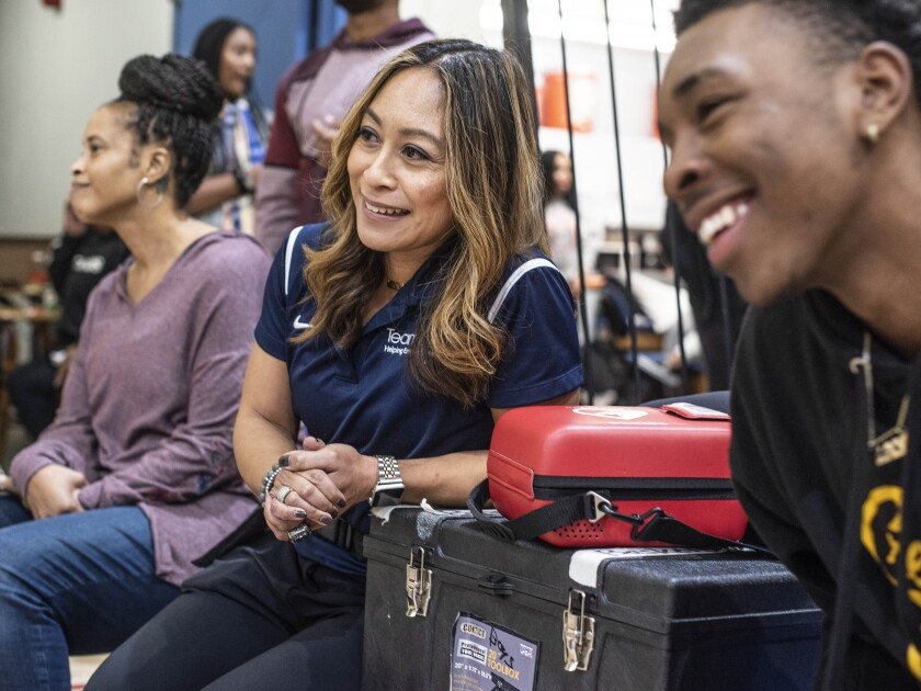 Crenshaw athletic trainer Ellen Kelly, watching the Cougars play a basketball game Friday, helped save the life of coach Ed Waters earlier this month when he collapsed along the sideline.