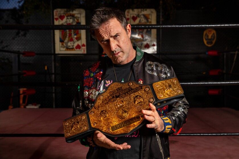 David Arquette holding his wrestling championship belt.
