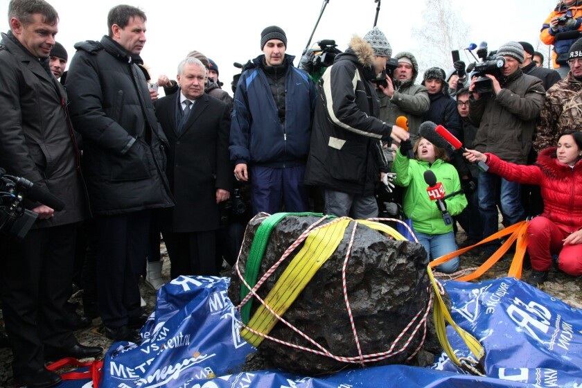 People look at what scientists believe to be a chunk of a meteor recovered from Russia's Chebarkul Lake. A meteor exploded over the area in February.