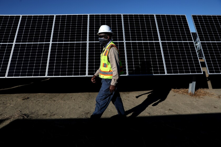 A man in a high-visibility vest walks in front of solar panels