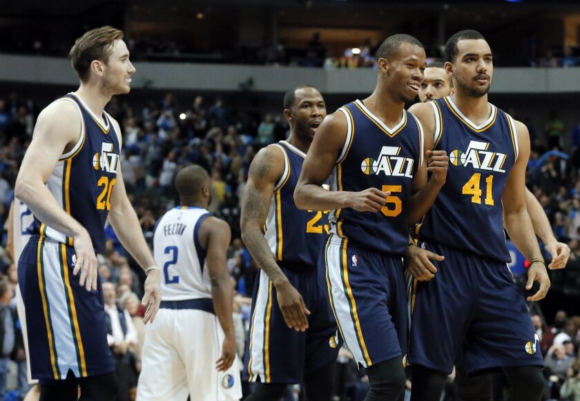 Utah Jazz's Gordon Hayward (20) , Rodney Hood (5), Trey Lyles (41) and Chris Johnson, rear, walk to the bench celebrating after Hood sank a 3-point basket late in the second half of an NBA basketball game against the Dallas Mavericks on Tuesday, Feb. 9, 2016, in Dallas. The shot tied up the game se