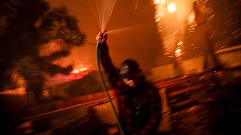 VENTURA, CALIF. -- TUESDAY, DECEMBER 5, 2017: Prescott McKenzie hoses down the roof as embers move w