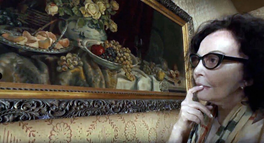 """Lilka Elbaum looks at a painting in a scene from the documentary """"Still Life in Lodz."""""""