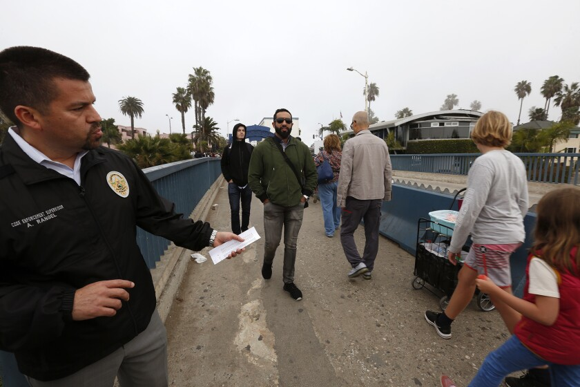Armando Rangel, left, a code enforcement supervisor for the city of Santa Monica, points to the cart of a street vendor on the Santa Monica Pier this month.