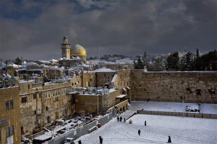 ARCHIVO- En esta foto del 13 de diciembre dle 2013, el Muro de los Lamentos, derecha, y la Cúpula de la Roca, entre los sitios más sagrados para judíos y musulmanes, están cubiertos de nieve. Israel suspendió el viernes, 14 de octubre del 2016, su colaboración con la UNESCO, un día después que la agencia cultural de la ONU adoptó un proyecto de resolución que Israel dice niega las profundas conexiones históricas de los judíos con lugares sagrados en Jerusalén.