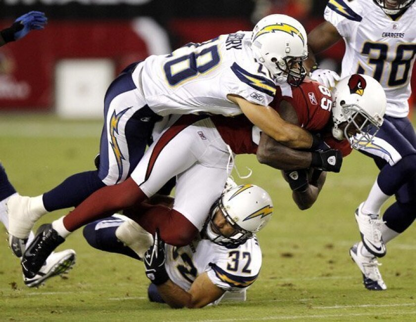 Arizona Cardinals' Early Doucet  is tackled by San Diego Chargers' Steve Gregory  and Eric Weddle  during the first half.