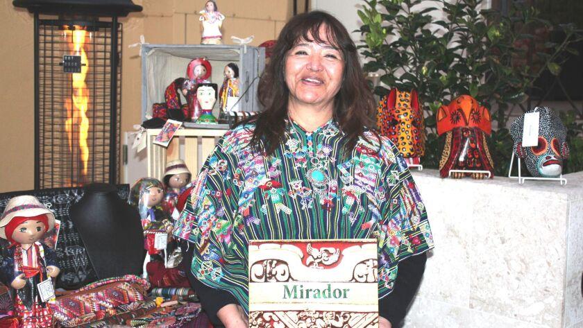 Bella Guatemala Travel owner Elsie YiDonoy poses with Richard Hansen's book 'El Mirador' at the Pantai Inn in La Jolla.
