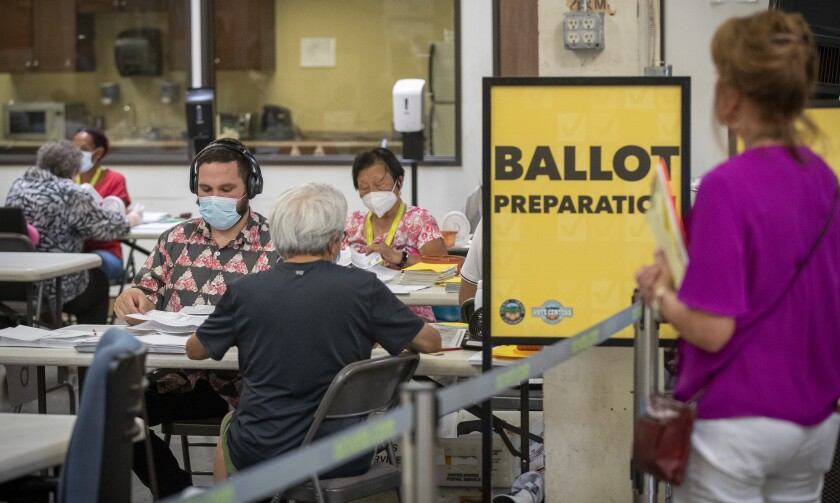 """A poll watcher observes election workers next to a sign that says """"Ballot preparation."""""""