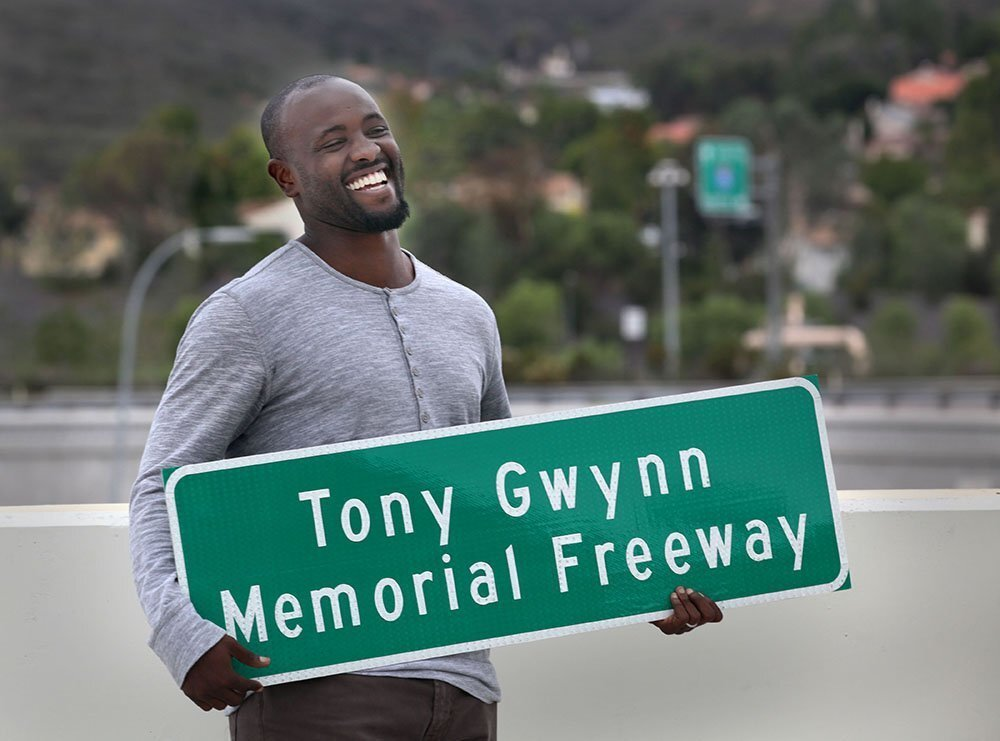 Tony Gwynn Jr. smiles broadly as he holds a replica sign made for him and his family, presented to them by Caltrans employees Monday during a ceremony unveiling new freeway signs namiing a section of Interstate 15 as Tony Gwynn Memorial Freeway.