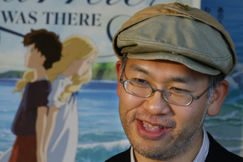 """In this Feb. 1, 2016 photo, Japanese director Hiromasa Yonebayashi speaks about his latest film """"When Marnie Was There"""" with its poster during an interview at his office, Studio Ghibli, in suburban Tokyo. The coming-of-age story is familiar: A shy girl has problems fitting in and concocts an imagin"""