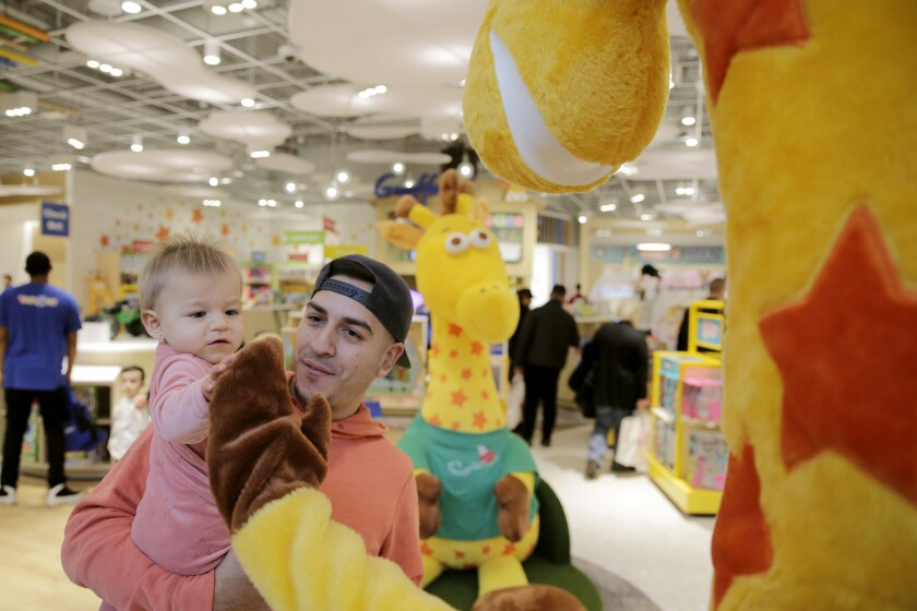 A father and baby greet Toys R Us mascot Geoffrey