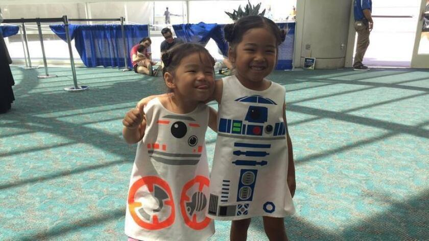 """Sisters Maeka, 3, and Ellie Yamamichi, 5, pose in their costumes for R2-D2 and BB-8 from """"Star Wars: The Force Awakens."""" (Abby Hamblin)"""
