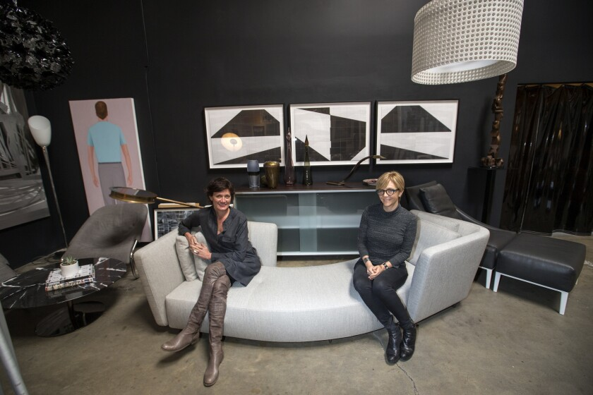 Stacia Vinar, left, and Sarah Whipple, owners of Modern Resale, sit among some of the modern European furniture, lighting and accessories at their Los Angeles showroom. The pieces are secondhand but inspected for quality.